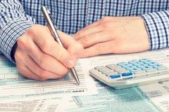 Steuerzahler, der 1040 Steuerformular ergänzt Gefiltertes Bild: Kreuz verarbeiteter Weinleseeffekt Lizenzfreie Stockfotografie