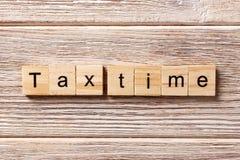 Steuerzeitwort geschrieben auf hölzernen Block Steuerzeittext auf Tabelle, Konzept Lizenzfreies Stockfoto