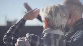 Steun van vrouw met grijs kort haar en rug van kale man status buiten en sluit met handen een gezicht van de sterke zon stock video