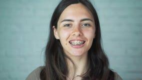 Steunen op de tanden De meisjesglimlachen die haar steunen op haar tanden tonen Witte en gezonde tanden stock videobeelden