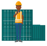 Stevedore standing on cargo containers background. Royalty Free Stock Photography