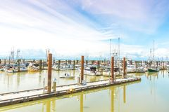 Boats and docks at Steveston Fisherman`s Wharf. STEVESTON, BRITISH COLUMBIA, CANADA - JUNE 2017: pier and boats in the marina by the famous Fisherman`s Wharf in Stock Image