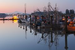 Steveston Calm Morning Reflections. In the early morning, commercial fishboats reflect in the calm water of Steveston Harbor, British Columbia near Vancouver Stock Photo
