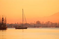Steveston Harbor Dawn Sailboat. Dawn in Steveston, British Columbia, Canada where a sailboat casts off for a day of sailing. Located at the mouth of the Fraser Stock Photography