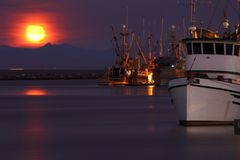 Steveston Harbor Moonset. A long exposure of Steveston Harbor In the early morning with commercial fishboats tied to the docks as the full moon sets behind the Stock Images
