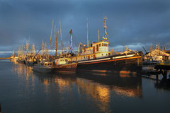 Steveston Storm Clouds, Richmond, BC. Dawn sunlight on boats against a background of storm clouds in Steveston, British Columbia, Canada near Vancouver Stock Image