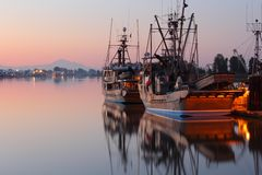 Steveston Wharf Dawn, British Columbia. Dawn at the marina in Steveston Harbor, British Columbia, Canada where the commercial fishing fleet waits for the fishing Royalty Free Stock Photo