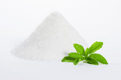 Stevia with a pile of sugar. Stevia leaves in front of a pile of sugar isolated on a white background Stock Photos