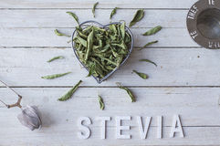 Stevia. Still Life with  bowl in the form of a heart, full of dried stevia leaves and the word stevia with white wooden letters Royalty Free Stock Photos