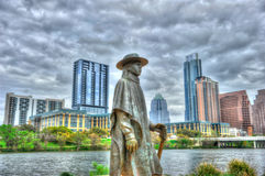 Stevie Ray Vaughan Memorial, Lady Bird Lake, Austin, Texas. Stevie Ray Vaughan Memorial on banks of Lady Bird Lake in downtown Austin, Texas with skyline in Royalty Free Stock Photography