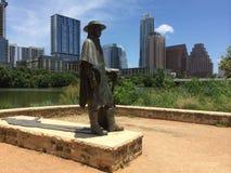 Stevie Ray Vaughan Statue med Austin Texas i bakgrund Fotografering för Bildbyråer
