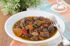 Stew of beef with vegetables and prunes in a plate Stock Photo