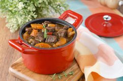 Stew of beef with vegetables and prunes in a red cast iron pan Stock Image
