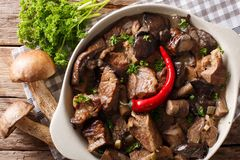 Stew beef with wild forest mushrooms and chili close-up. Horizon Royalty Free Stock Photo