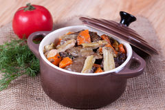 Stew in a ceramic pot. On the desk Stock Photography