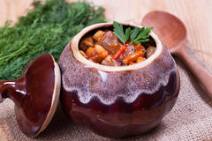 Stew in a ceramic pot. On the desk Royalty Free Stock Photography