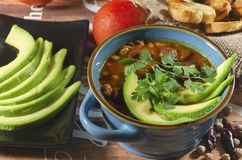 Chorizo ​​and chickpea stew. Stew of chorizo ​​and chickpeas, on a blue plate with avocado and toast garnished with cilantro on a stock photography