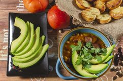 Chorizo ​​and chickpea stew. Stew of chorizo ​​and chickpeas, on a blue plate with avocado and toast garnished with cilantro on a stock photos