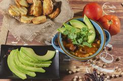 Chorizo ​​and chickpea stew. Stew of chorizo ​​and chickpeas, on a blue plate with avocado and toast garnished with cilantro on a royalty free stock photos