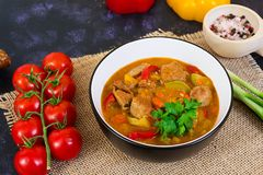Stew with meat and vegetables in tomato sauce on dark background.  royalty free stock photos