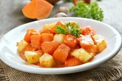 Stew pumpkin and potato. On white plate Stock Image