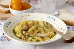 Stew or roast or soup with meat and potatoes, served with canned tomatoes and bread. stock images