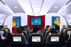 Steward (hôtesse de l'air) montrant la procédure de sécurité aux passagers illustration libre de droits