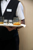 Steward in hotel. Steward with drinks in hand waiting guests Royalty Free Stock Photo