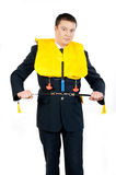 Steward in a life jacket. Male steward showing how to use a life jacket Stock Image