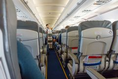 Steward offers food and drinks to economy class passengers. On the plane Royalty Free Stock Image
