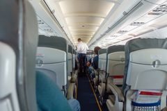 Steward offers food and drinks to economy class passengers. On the plane Stock Image