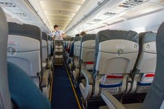 Steward offers food and drinks to economy class passengers. On the plane Royalty Free Stock Images
