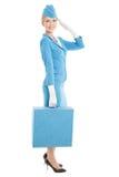 Stewardess в голубых форме и чемодане на Whit стоковые фотографии rf