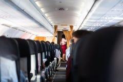 Stewardess в красной форме на коммерчески самолете пассажиров стоковая фотография rf