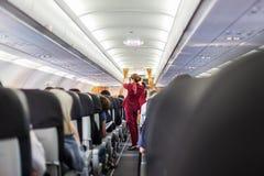Stewardess в красных равномерных давая инструкциях по безопасности на коммерчески самолете пассажиров стоковые изображения