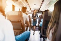 Stewardess представляет на шине Оно стоит между строками мест на которых пассажиры сидят Стоковое Фото