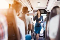 Stewardess представляет на шине Оно стоит между строками мест на которых пассажиры сидят Стоковая Фотография RF