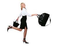 Stewardess. Nice blond smiling girl in white shirt and black skirt running with bags in her hands Royalty Free Stock Images