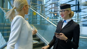 Stewardess at the airport with a phone in her hands helps passenger. stock footage