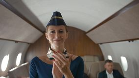 Stewardess applause to camera inside of private business jet cabin