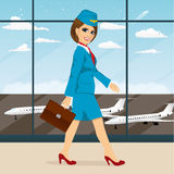 Stewardess with briefcase walking through airport terminal Royalty Free Stock Image