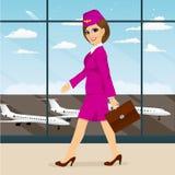Stewardess with briefcase walking through airport terminal Stock Image