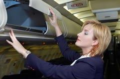 Stewardess, der Gepäck überprüft Lizenzfreie Stockfotografie
