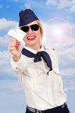 Stewardess, der Papierflugzeug hält Stockfotografie