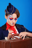 Stewardess with face art baggage checks. Royalty Free Stock Photo