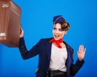 Stewardess with face art luggage holds. Stock Photo