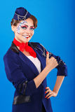 Stewardess with face art shows thumb up. Royalty Free Stock Photo