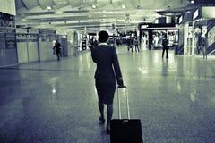 Stewardess am Flughafen mit einem Koffer stockbilder