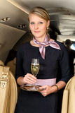 Stewardess with the glass of champagne Royalty Free Stock Photography