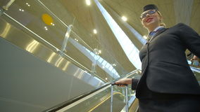 Stewardess with glasses on his face coming down the escalator. Stewardess with glasses on her face down on the escalators from below. Woman dressed in dark stock footage
